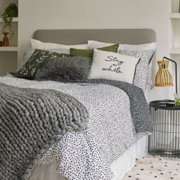 A double bed topped with a polka dot duvet set, sage green chunky knitted throw and a selection of white and sage green accent cushions.
