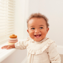 A laughing baby wearing a cream dress with frill details.