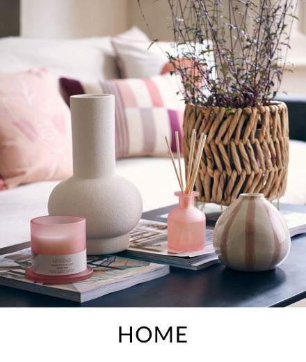 A coffee table topped with grey vases, pink candle, pink reed diffuser and a wicker planter.