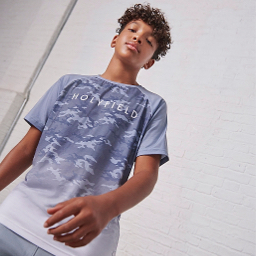 A boy wearing a blue camo print HOLYFIELD top.