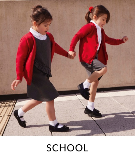 Two girls skipping outdoors, both in white school shirts, grey school dresses, red school cardigans and black school shoes.