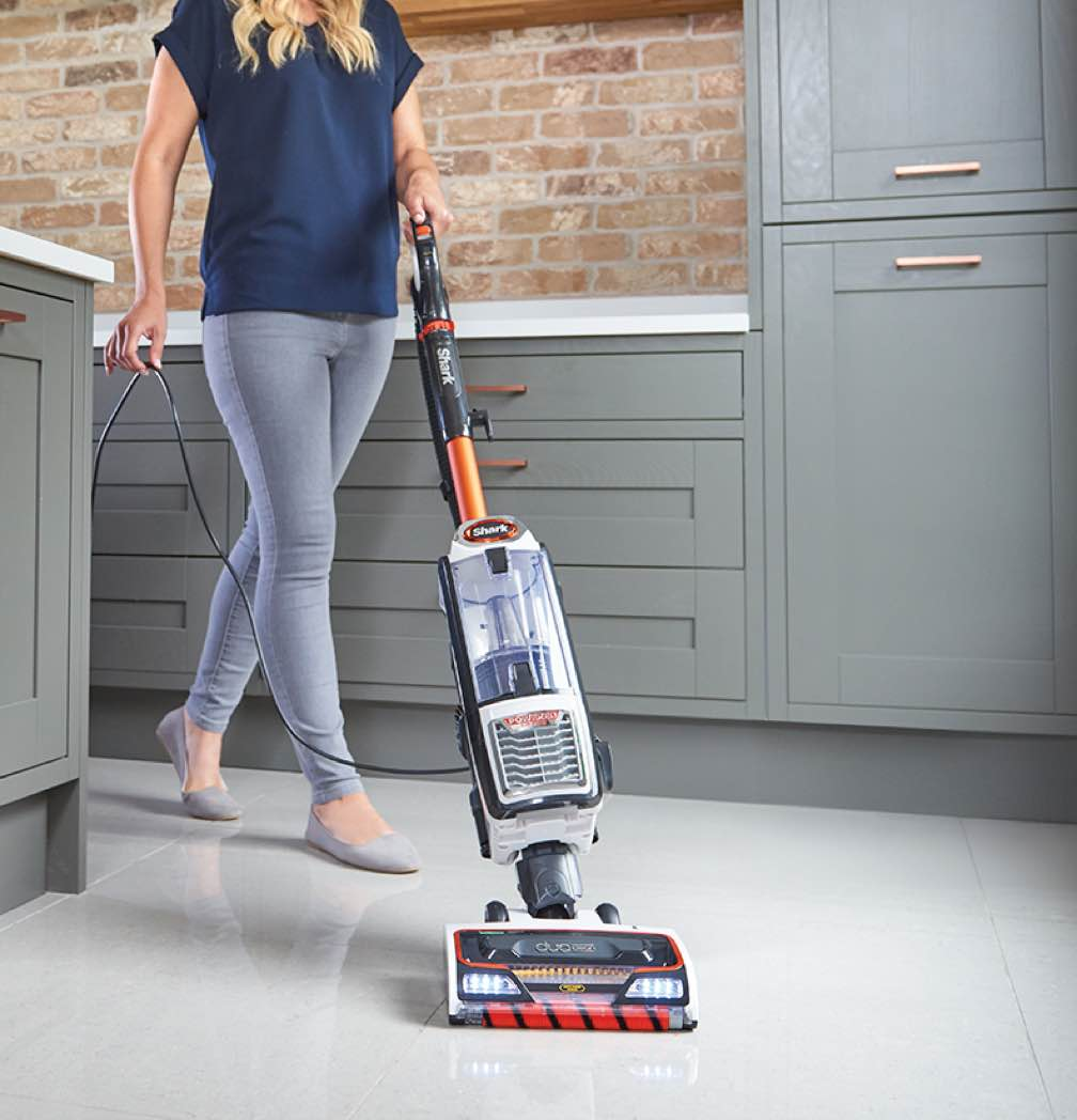 A woman using a Shark Corded Vacuum in a kitchen.