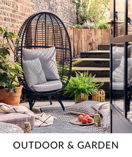 A black chair with grey cushions in a garden surrounded by potted plants, cushions and throws.