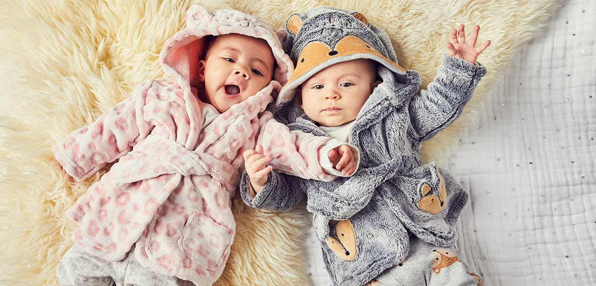 Two babies lying next to each other on a faux fur throw, one wearing a pink hooded dressing gown, the other a grey hooded dressing gown