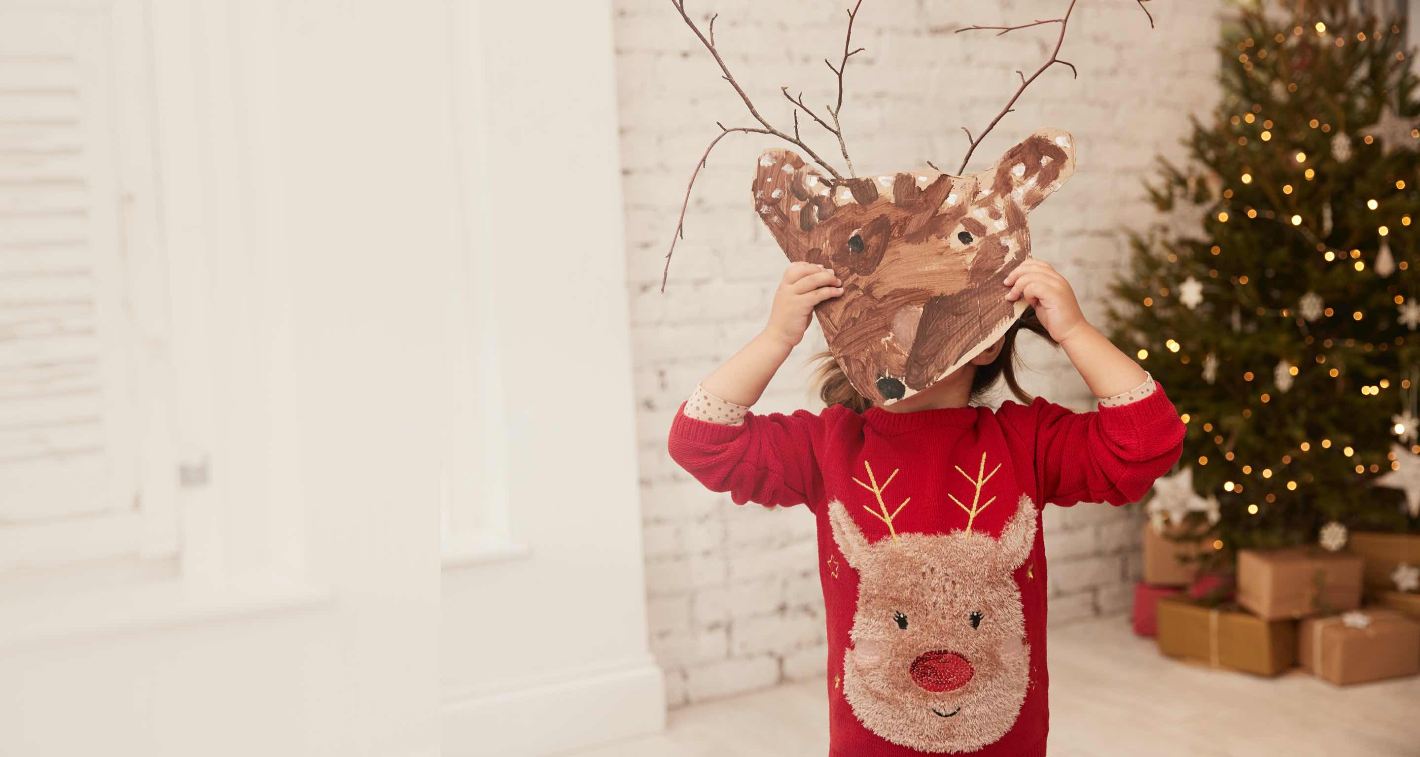 Little girl wearing a red reindeer fluffy jumper holding up a hand painted reindeer mark with twigs for antlers.