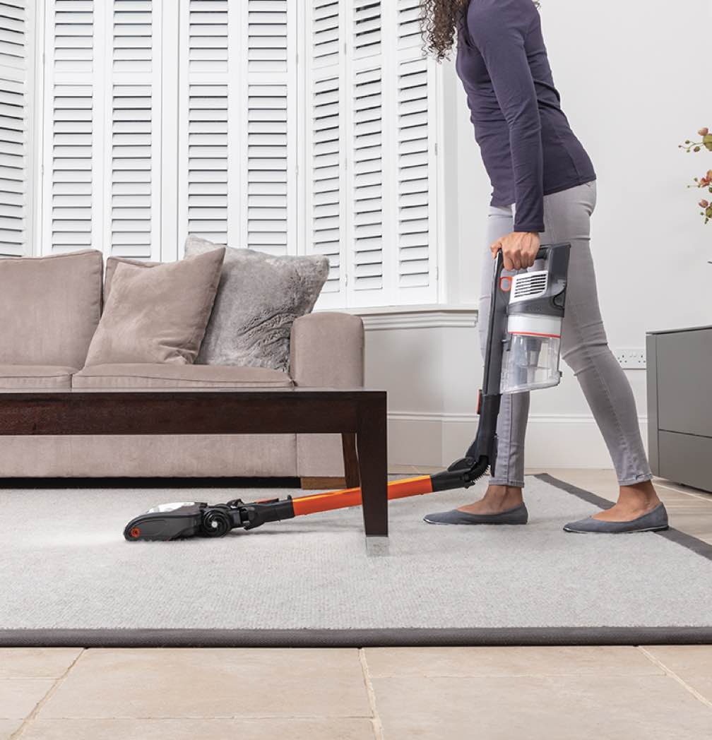 A woman using a Shark Cordless Vacuum under a coffee table in a living room.